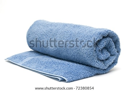 A blue towel rolled up on a white background - stock photo