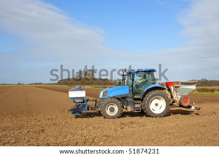 a blue tractor applying pesticides and cultivating soil in springtime under a blue sky