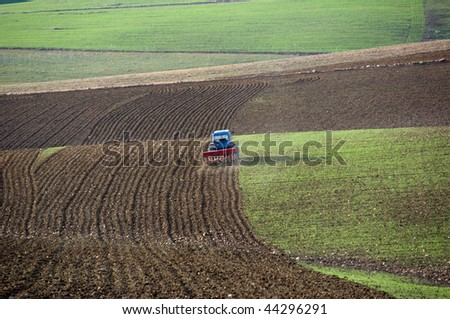 a blue tractor with a plow furrows the earth - stock photo