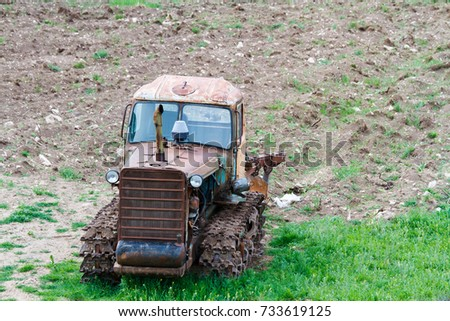 A blue tractor working in the green field.