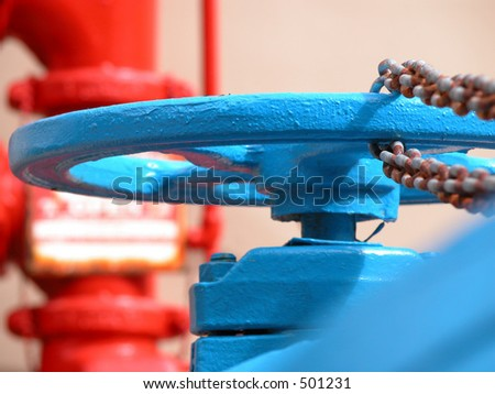 A blue water hydrant with a rusted chain and a red meter in the background.
