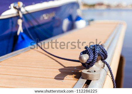 A blue yacht moored with a line tied around a fixing on the quayside/ Mooring at a pier - stock photo