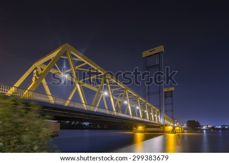 A blue-yellow lift bridge in the Port at night