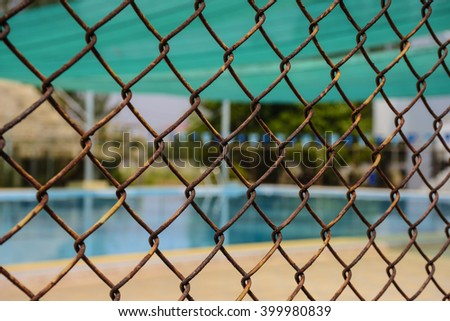 a blur picture of a swimming pool behind the wire mesh.