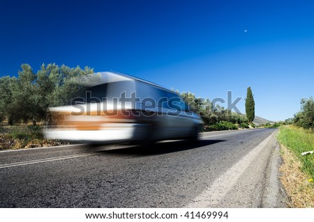 a blurred car speeding on the country road - stock photo