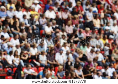 A blurred crowd of spectators in a stadium at a sporting event. - stock photo