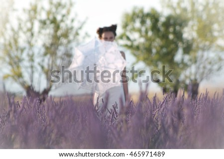 A blurred dream of girl with an umbrella among lavender flowers.