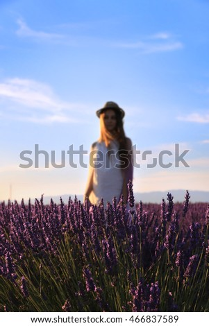 A blurred figure of a girl standing behind rows of lavender flowers.