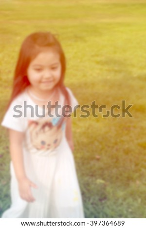 A blurred happy little girl wearing white dress and  running at public park with greenery background. Vintage filtered color tone - stock photo