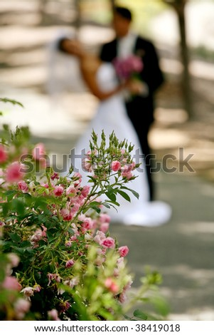 A blurred image of a newly wed with flowers in the foreground - stock photo