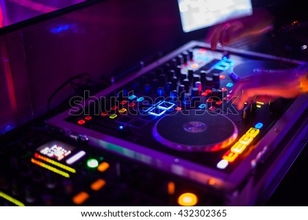 A blurred purple DJ working on his turntables - stock photo