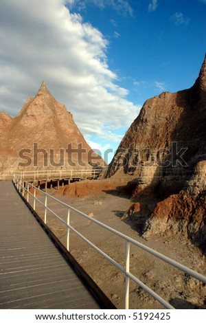 A boardwalk allows tourists to walk in the sensitive areas of the Badlands National Park in South Dakota. - stock photo
