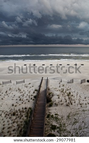 A boardwalk leading to the beach under storm clouds in Gulf Shores AL. - stock photo