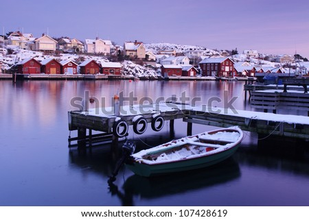 A boat and a jetty in the winter, Sweden. - stock photo