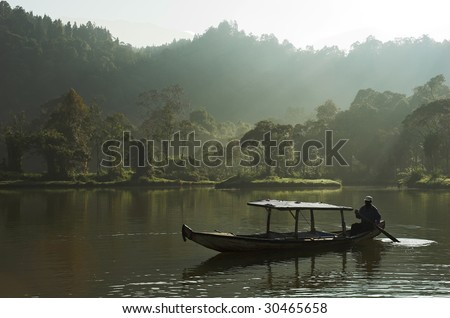 A boat and sailor on a lake in the middle of rain forest. Situ Gunung - Indonesia