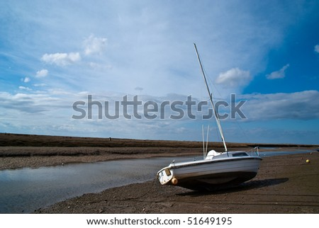 A boat at Blakeney Harbour in Norfolk, England on slipway against a blue sky - stock photo