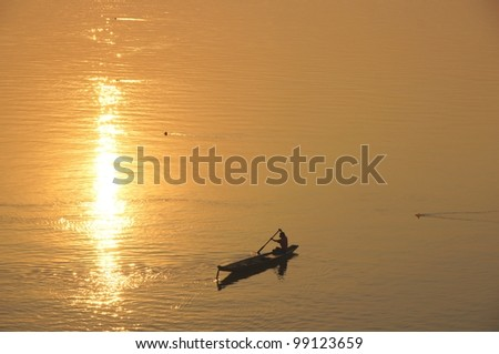 A boat crossing the Mekong River at sunset. Four thousand islands in Laos - stock photo