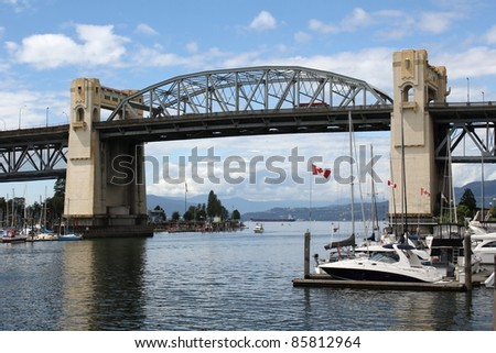 A boat enters False Creek approaching the historic Burrard Street bridge in downtown Vancouver. British Columbia, Canada. - stock photo