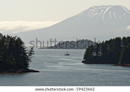 A boat fishes in Sitka Sound under Mount Edgecombe, Alaska. - stock photo