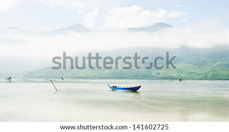 A boat in the middle on a large lake - stock photo