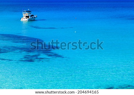A boat in turquise water near the shore of Cyprus - stock photo