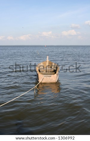 A boat in water tied up with a rope