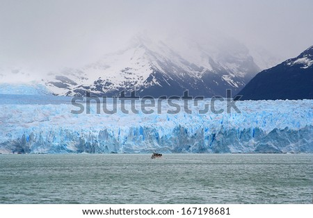 a boat is navigating to the occidental side of the perito moreno glacier - stock photo