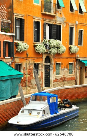 a boat is parked up against a footpath in Venice. Flowers in window boxes of an overlooking house. - stock photo