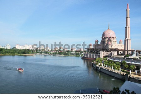 A boat is passing the lake next to a beautiful mosque - stock photo