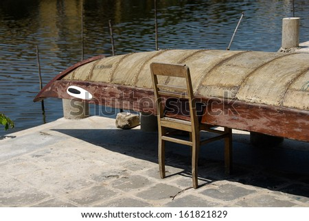 A boat is resting on a chair along side the water. - stock photo