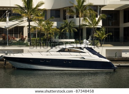 A boat moored beside a luxury home, Surfers Paradise, Queensland, Australia - stock photo