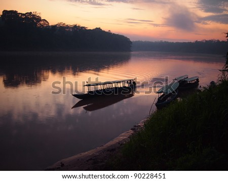 A boat navigating the Tambopata jungle river during a purple and pink sunrise with reflection in the water in the Amazon rainforest in eastern Peru. - stock photo