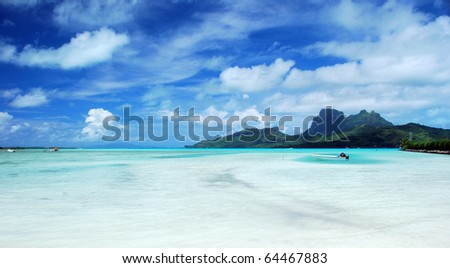 a boat on the turquoise lagoon with otemanu mountain view behind - stock photo