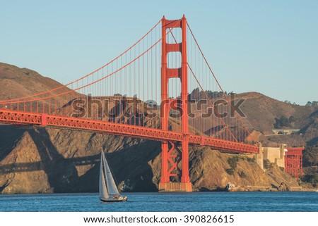 A boat travelling under the Golden Gate Bridge in San Francisco, California, USA  - stock photo