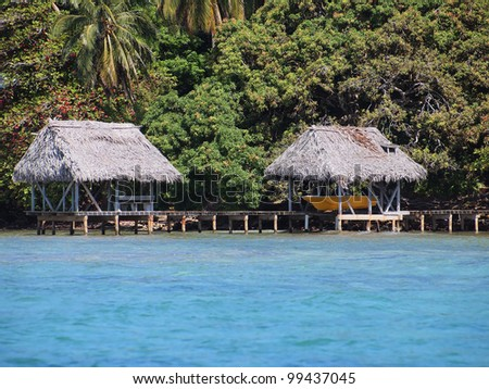 A boathouse and palapa on stilts over the sea with lush tropical vegetation in background - stock photo