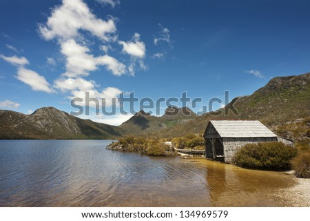 A boathouse sits on the edge of Dove Lake with Cradle Mountain in the background.  Tasmania, Australia. - stock photo
