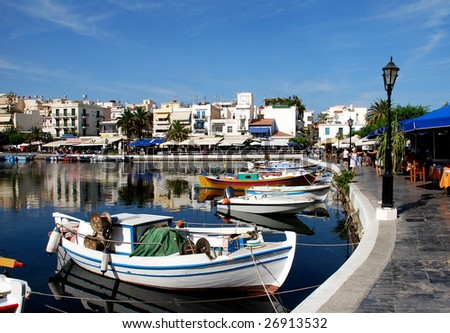 A boats next to a taverna at Aghios Nikolaos lake, Crete. - stock photo