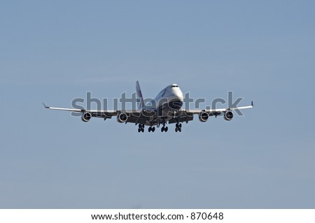 A Boeing 747 coming in for landing with it's gears down. - stock photo