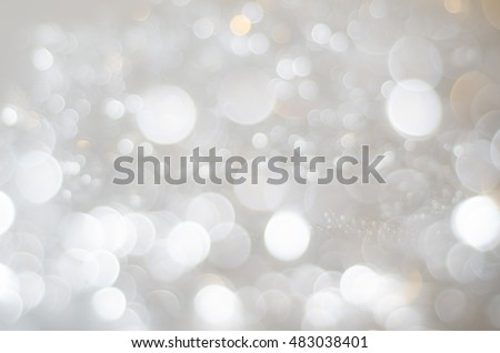 A bokeh texture background of large and small circles in whites, silver greys and soft copper gold.