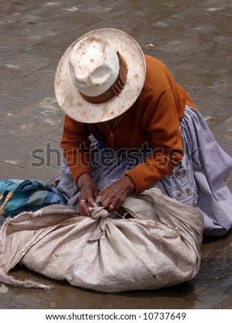 A bolivian market woman is getting her stuff out - stock photo