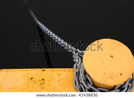 A bollard and chain used for typing up boats - stock photo