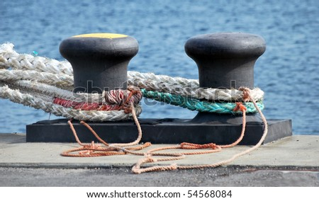 a bollard at the water in a harbor - stock photo