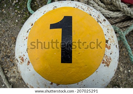 A bollard for mooring ships with a large number one painted on it.  Southampton docks. - stock photo