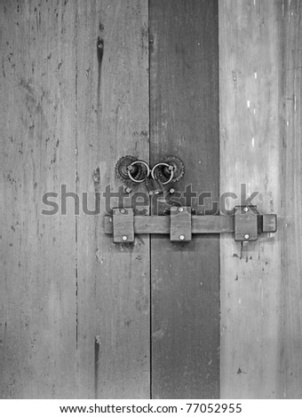 A bolt lock and padlock on a rustic solid vintage timber door in black and white.