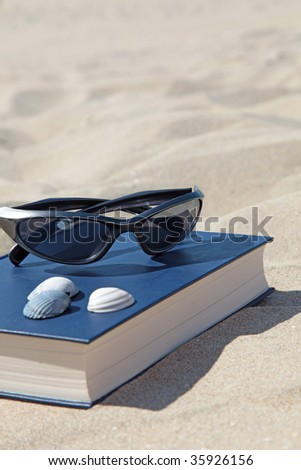 A book and sunglasses lying in the sand, symbolizing recreation