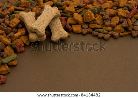 A border made of dog food and dog treats on brown background, doggy food - stock photo