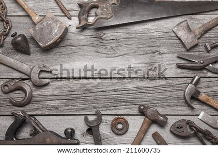 A border made up of vintage tools on a background of grey barnboard. - stock photo