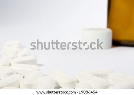 A border of pills on the left-hand side and lower part of a white frame with an opend bottle in the top right-hand area