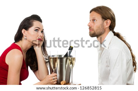A bored couple out on a Champagne date avoiding eye contact. Isolated on white.