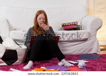 A bored girl yawning when studing for school at home - stock photo
